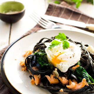 Czarny makaron z łososiem i jajkiem w koszulce